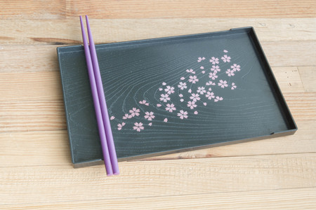 Purple chopsticks on black tray Sakura's design wooden background Foto de archivo