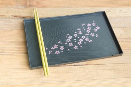 Yellow chopsticks on black tray Sakura's design wooden background