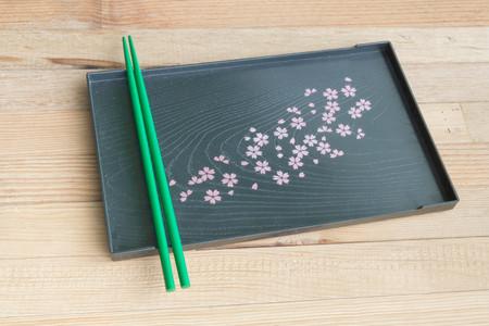 Green chopsticks on black tray Sakura's design wooden background