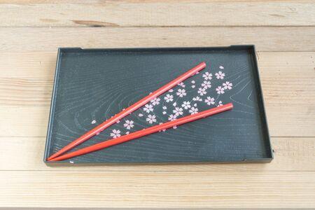 Red chopsticks on black tray Sakura's design wooden background