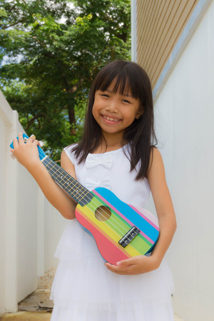 Young asian funny girl having fun and playing on small colorful ukulele guitar Stock fotó