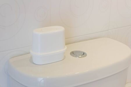 health care facilities: Perfume bottle on white toilet bowl in a bathroom
