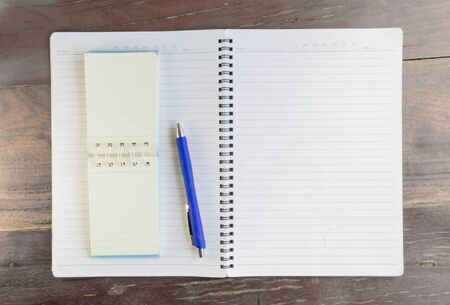Blank notebook and pen on old wooden office desk. Stock Photo