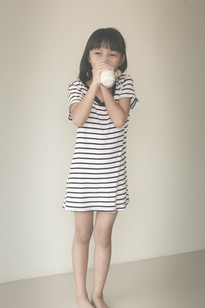 encouraged: Gorgeous little girl wearing striped encouraged to drink milk - Vintage Filter Effect Stock Photo