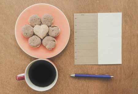 blue pen: Memory blank notebook and blue pen with coffee and cookie on wooden background - Vintage Filter Effect