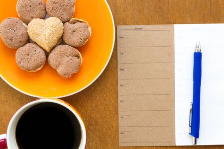 blue pen: Memory blank notebook and blue pen with coffee and cookie on wooden background