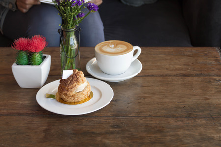 french fancy: Eclair coffee cream in a dish on a wooden floor. Stock Photo