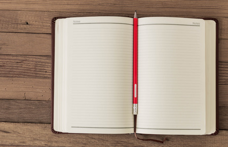 Note blank open book with orange pencil on textured wood background