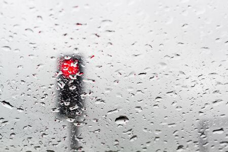 Abstract Blur - Traffic light on a rainy day window background Stock Photo