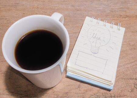 hardwoods: White Cup of coffee and litter notebook with word Idea on the table. Stock Photo