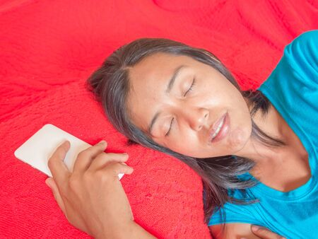red bed: Asian blue shirt woman sleeping with white smart phone on the red bed.