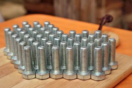 la union hace la fuerza: nudos de acero en el fondo de madera Foto de archivo