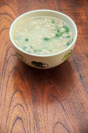 Thai style of rice gruel in bowl on the wood table photo
