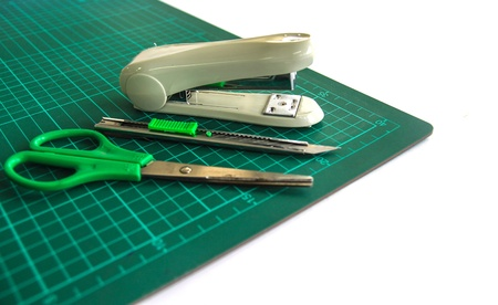 A pair of scissors , cutter and stapler  on a green cutting mat photo