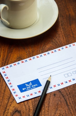 Air mail envelope on wooden table with pencil and coffee cup photo