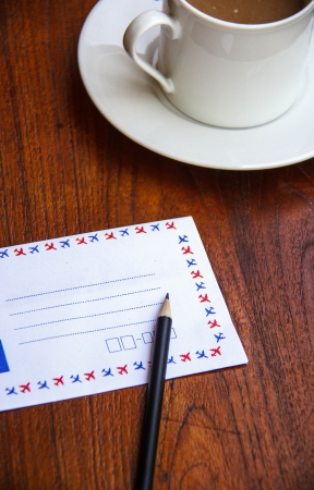 Blank envelopes on wooden table with pencil and coffee cup photo