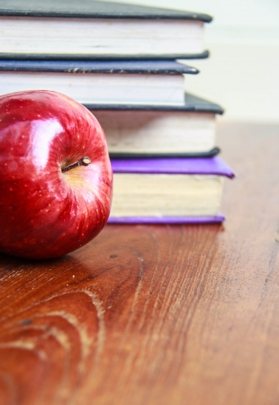 red apple and  old books  on wooden tabletop photo