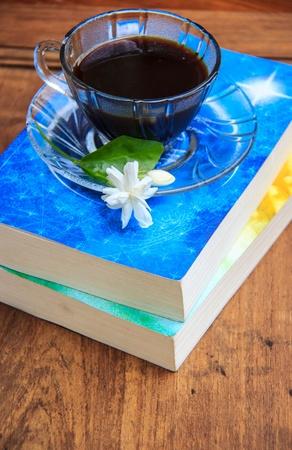 jasmine flower: black coffee on wooden table with books and Jasmine flower