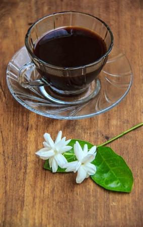 jasmine flower: black coffee on wooden table with Jasmine flower