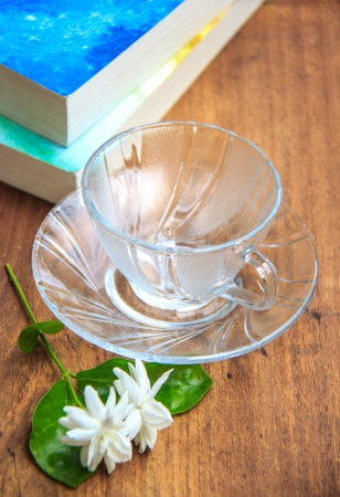 jasmine flower: coffee cup on wooden table with books and Jasmine flower