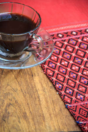 red tablecloth: black coffee on wooden table with handmade red tablecloth Thai style