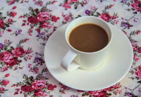 coffee  on  table with book  and rose bouquet  fabric as background photo