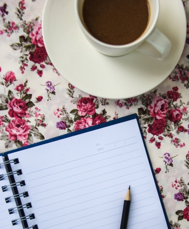blue notebook on the table with pencil and coffee cup photo
