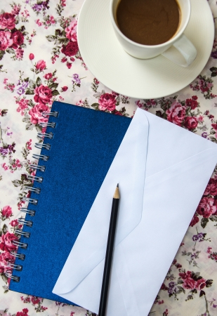 Blank envelopes on the table with pencil and coffee cup and blue notebook photo