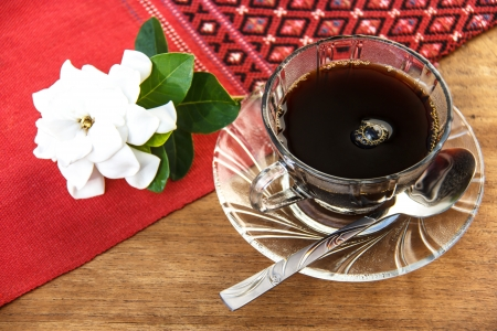 red tablecloth: black coffee on the table with Gardenia angusta flower and handmade red tablecloth Thai style