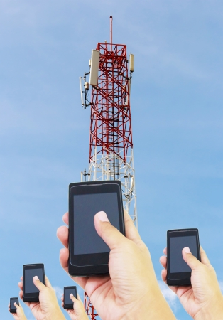 Hand holding smart phone and Telecommunications tower with satellite dish , Bule sky Background photo