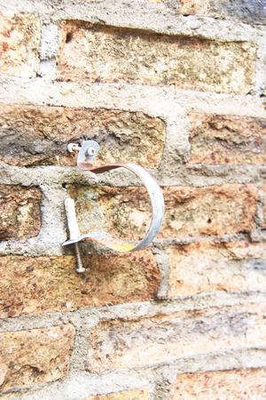 bri: Pipe straps on old concrete vintage brick wall background Stock Photo