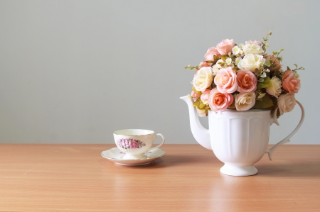 Romantic  a bouquet of roses in white  jug with coffee cup on wooden table  and gray concrete walls photo