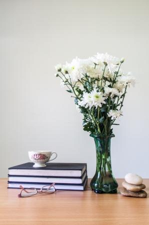 ロマンチックな木製のテーブルと灰色のコンクリートの壁にガラスと石の古い本とコーヒー カップとグリーン ガラス水差しの菊白の花束