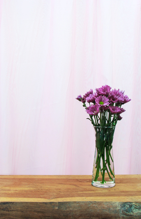Romantic  a bouquet of Chrysanthemum purple  in glass  jug  on wooden table  and pink cloth background photo