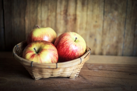 Red apple on wooden table with gray wall photo