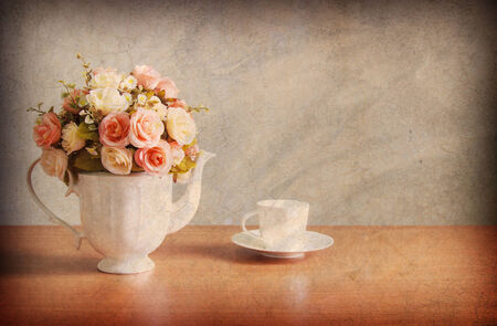 Abstract old background with romantic a bouquet of roses in white  jug with coffee cup on wooden table and concrete walls.For art texture, grunge design, and vintage cement wall or border frame photo