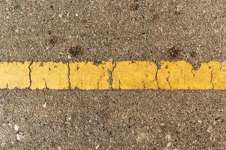 黄色ラインが、大まかなアスファルトの道路の背景古いテクスチャです。
