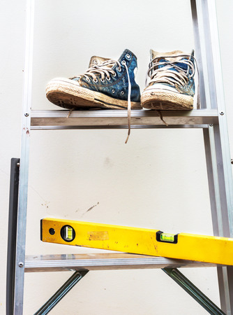 Water level  and Blue sneakers on Aluminium ladder with wall dirty photo