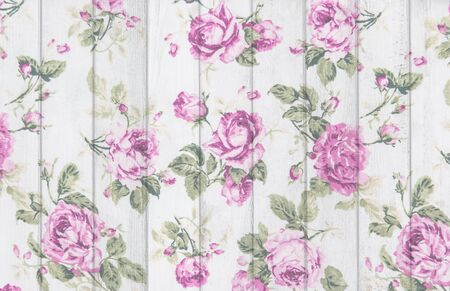 pink rose vintage from fabric on white wooden background.