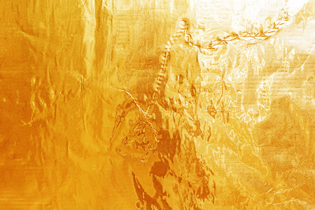crease: Shiny yellow leaf gold foil texture for background. Crease