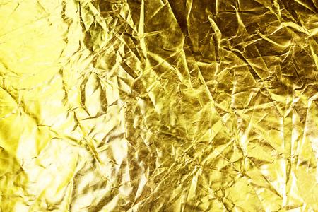 金の背景色またはテクスチャと影。金の生地のしわ。
