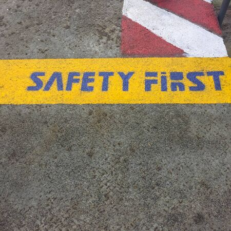 safety first: Safety first text on floor. Stock Photo