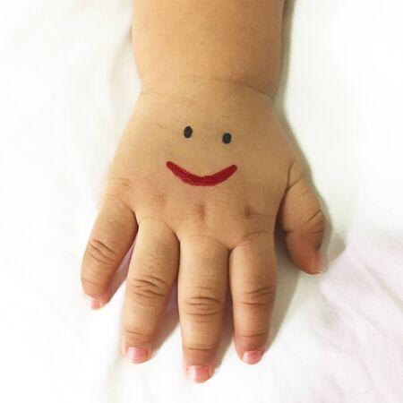 Sourire dessiné à la main, petit garçon. 1 an.