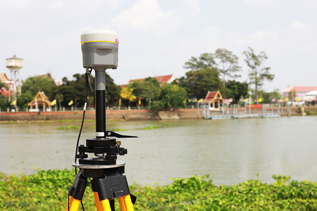 GPS surveying in field river background, Global Positioning System.