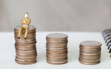 Figure miniature businessman or small people sit on money coin and book background for money and financial business shopping concept. Reklamní fotografie - 127110884