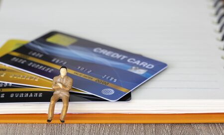 Figure miniature businessman or small people sit on credit card and book background for money and financial business shopping concept. Reklamní fotografie
