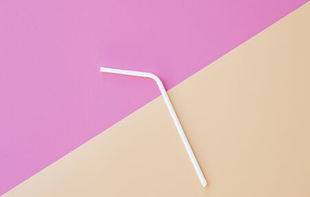 straw white plasticl on pink - peach background and copy space