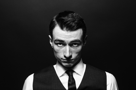 Close up black and white portrait of a young man in a white shirt, black tie and vest, seriously looking at the camera, against plain studio background