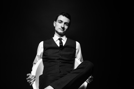 Close up black and white portrait of a young man in a white shirt, black tie and vest, sitting and looking at the camera, against plain studio background