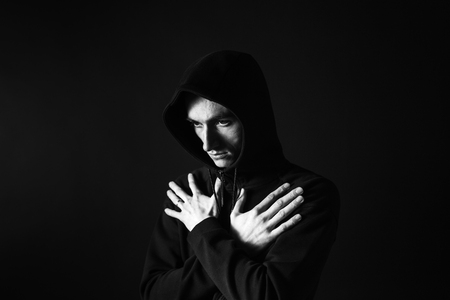 Black and white studio headshot of a young man in a black sweatshirt, hands on chest, against plain studio background Stock Photo